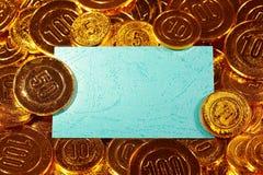 Μπλε κάρτα εγγράφου του Κραφτ στο χρυσό σωρό νομισμάτων Στοκ Εικόνες
