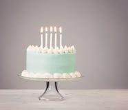 Μπλε κέικ γενεθλίων πέρα από το γκρίζο υπόβαθρο Στοκ Εικόνα
