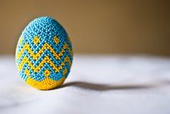 Μπλε-κίτρινο pysanka στο τραπεζομάντιλο Στοκ Εικόνα
