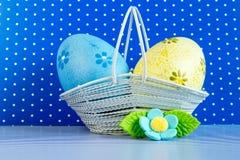 Μπλε και κίτρινα αυγά Πάσχας σε ένα καλάθι με το μπλε λουλούδι Στοκ φωτογραφίες με δικαίωμα ελεύθερης χρήσης