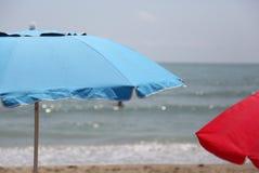 Μπλε και κόκκινες ομπρέλες παραλιών στην παραλία θαλασσίως το καλοκαίρι Στοκ Φωτογραφία