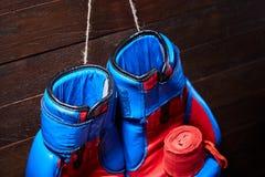Μπλε και κόκκινοι εγκιβωτίζοντας γάντια και επίδεσμος στο καφετί υπόβαθρο σανίδων Στοκ φωτογραφία με δικαίωμα ελεύθερης χρήσης
