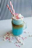 Μπλε καφές με την κρέμα, marshmallow και τη ζωηρόχρωμη διακόσμηση σε ένα γραπτό υπόβαθρο Κούνημα γάλακτος Στοκ φωτογραφία με δικαίωμα ελεύθερης χρήσης