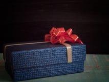 Μπλε κιβώτιο δώρων με το τόξο κορδελλών, που τίθεται στο ξύλινο πάτωμα Στοκ εικόνες με δικαίωμα ελεύθερης χρήσης