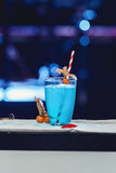 Μπλε κοκτέιλ με τον πάγο και τους σωλήνες, μπλε πίσω φω'τα Στοκ Εικόνα