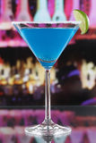 Μπλε κοκτέιλ του Κουρασάο Martini στο γυαλί σε έναν φραγμό Στοκ Φωτογραφία