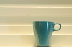 Μπλε κούπα στο άσπρο υπόβαθρο βημάτων Στοκ Εικόνες