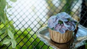 Μπλε κρέμα σχεδίου cupcake όπως το μπλε λουλούδι Hydrangea στο υπόβαθρο δακρυ'ων κιγκλιδωμάτων χάλυβα Στοκ φωτογραφία με δικαίωμα ελεύθερης χρήσης