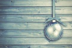 Μπλε μπιχλιμπίδια Χριστουγέννων με τη σγουρή κορδέλλα σε έναν μπλε ξύλινο πίνακα Στοκ Εικόνες