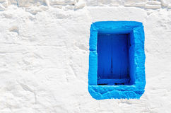 Μπλε ξύλινο παράθυρο στον άσπρο τοίχο πετρών, Ελλάδα Στοκ εικόνα με δικαίωμα ελεύθερης χρήσης