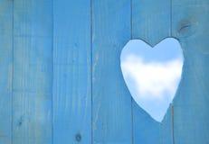 Μπλε ξύλινο υπόβαθρο επιτροπής με διαμορφωμένη την καρδιά τρύπα Στοκ Φωτογραφία