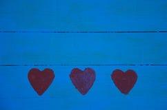 Μπλε ξύλινο υπόβαθρο επιτροπής με τις κόκκινες καρδιές Στοκ Φωτογραφίες