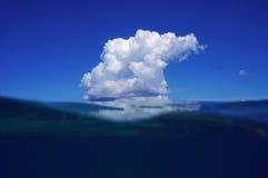 Μπλε ουρανός και θάλασσα που χωρίζονται από την ίσαλη γραμμή με ένα σύννεφο Στοκ Εικόνες