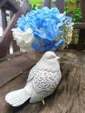 Μπλε λουλούδι Hydragea και γλυπτό πουλιών στον ξύλινο πάγκο Στοκ Φωτογραφίες