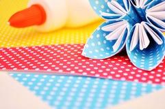 Μπλε λουλούδι origami και μπουκάλι κόλλας στο διαστιγμένο υπόβαθρο Στοκ Εικόνες
