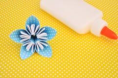 Μπλε λουλούδι origami και μπουκάλι κόλλας στο κίτρινο υπόβαθρο Στοκ φωτογραφία με δικαίωμα ελεύθερης χρήσης