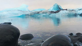 Μπλε παγόβουνα στο τρεχούμενο νερό στην παγετώδη λιμνοθάλασσα Jokulsarlon, Ισλανδία φιλμ μικρού μήκους