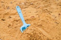 Μπλε παιχνίδι φτυαριών παιδιών στην άσπρη άμμο, πλαστικό παιχνίδι για το παιχνίδι Ανάχωμα της άμμου στον παιδικό σταθμό Στοκ Εικόνες
