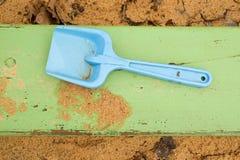 Μπλε παιχνίδι φτυαριών παιδιών στην άσπρη άμμο, πλαστικό παιχνίδι για το παιχνίδι Ανάχωμα της άμμου στον παιδικό σταθμό Στοκ Φωτογραφία