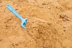 Μπλε παιχνίδι φτυαριών παιδιών στην άσπρη άμμο, πλαστικό παιχνίδι για το παιχνίδι Ανάχωμα της άμμου στον παιδικό σταθμό Στοκ φωτογραφία με δικαίωμα ελεύθερης χρήσης
