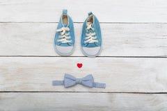 Μπλε παπούτσια για ένα μικρό μωρό και έναν πεταλούδα-δεσμό στο ξύλινο backgr Στοκ φωτογραφία με δικαίωμα ελεύθερης χρήσης