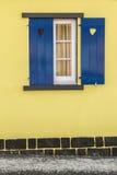 Μπλε παράθυρο με τις καρδιές και τον κίτρινο τοίχο Στοκ Εικόνα