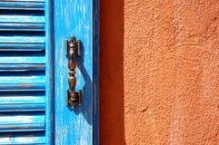 Μπλε παράθυρο στον πορτοκαλή τοίχο Στοκ εικόνα με δικαίωμα ελεύθερης χρήσης