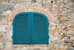 Μπλε παραθυρόφυλλα σε έναν αρχαίο Tuscan πέτρινο τοίχο στοκ εικόνες