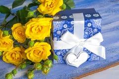 Μπλε παρόν κιβώτιο και κίτρινα τριαντάφυλλα στον ξύλινο δίσκο Στοκ Εικόνα