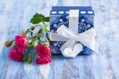 Μπλε παρόν κιβώτιο και ρόδινα τριαντάφυλλα στον ξύλινο δίσκο Στοκ εικόνες με δικαίωμα ελεύθερης χρήσης