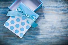 Μπλε παρόν κιβώτιο με ένα τόξο στην ξύλινη έννοια διακοπών πινάκων Στοκ Φωτογραφίες