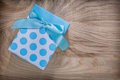 Μπλε παρόν κιβώτιο με το τόξο στην ξύλινη έννοια εορτασμών πινάκων Στοκ φωτογραφία με δικαίωμα ελεύθερης χρήσης