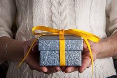 Μπλε παρόν με την κίτρινη κορδέλλα στα χέρια οριζόντια Στοκ Εικόνες