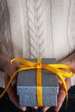 Μπλε παρόν με την κίτρινη κορδέλλα στην κατακόρυφο χεριών Στοκ Εικόνες
