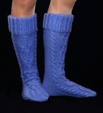 Μπλε περικνημίδες από το μαλλί στα θηλυκά πόδια στοκ εικόνα