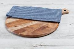 Μπλε πετσέτα στο στρογγυλό τεμαχίζοντας πίνακα Στοκ εικόνα με δικαίωμα ελεύθερης χρήσης