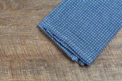 Μπλε πετσέτα τσαγιού στον ξύλινο πίνακα Στοκ εικόνες με δικαίωμα ελεύθερης χρήσης