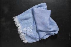 Μπλε πετσέτα χεριών με τα άσπρα περιθώρια στη σκοτεινή επιφάνεια Στοκ Φωτογραφίες