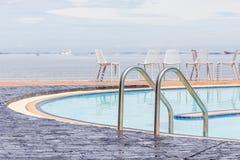 Μπλε πισίνα με τις καρέκλες παραλιών χαλάρωσης στο υπόβαθρο Στοκ εικόνες με δικαίωμα ελεύθερης χρήσης