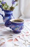 Μπλε ποτό ραδικιού τσαγιού φλιτζανιών του καφέ με το λουλούδι ραδικιού, καυτό ποτό στο κεντημένο υπόβαθρο υφάσματος Στοκ Φωτογραφία