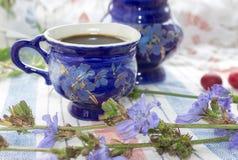 Μπλε ποτό ραδικιού τσαγιού φλιτζανιών του καφέ με το λουλούδι ραδικιού, καυτό ποτό στο κεντημένο υπόβαθρο υφάσματος Στοκ Εικόνες
