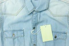 Μπλε πουκάμισο Jean με την κενή ετικέττα για το υπόβαθρο Στοκ Φωτογραφία