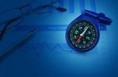 Μπλε πυξίδα με τη μάνδρα και γυαλιά στο οικονομικό διάγραμμα αύξησης και στοκ φωτογραφία με δικαίωμα ελεύθερης χρήσης