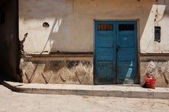 Μπλε πόρτα με τον κόκκινο κάδο Στοκ Εικόνες