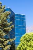 Μπλε πύργος γυαλιού πίσω από τα πράσινα δέντρα Στοκ φωτογραφίες με δικαίωμα ελεύθερης χρήσης