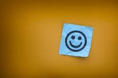 Μπλε σημείωση εγγράφου με το ευτυχές πρόσωπο σε ένα κίτρινο υπόβαθρο εγγράφου Στοκ εικόνες με δικαίωμα ελεύθερης χρήσης