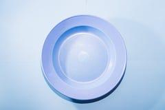 Μπλε στρογγυλό πιάτο στο μπλε υπόβαθρο Στοκ Εικόνα