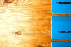Μπλε σχολικά σημειωματάρια σε έναν ξύλινο πίνακα Στοκ Εικόνα