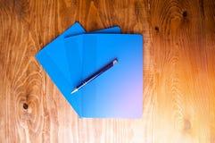 Μπλε σχολικά σημειωματάρια σε έναν ξύλινο πίνακα Στοκ φωτογραφίες με δικαίωμα ελεύθερης χρήσης