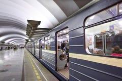 Μπλε τραίνο με τους επιβάτες που στέκονται κοντά στην πλατφόρμα στον υπόγειο STAT Στοκ Εικόνες